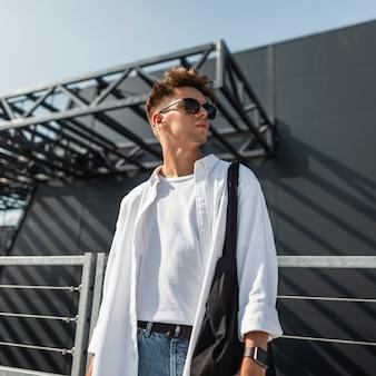 Aantrekkelijke jonge man in stijlvol wit overhemd in modieuze zonnebril in trendy spijkerbroek met een zwarte doek tas poseren op een zonnige dag in de buurt van een grijs gebouw buitenshuis. amerikaans jongensmodel. jeugd zomerstijl