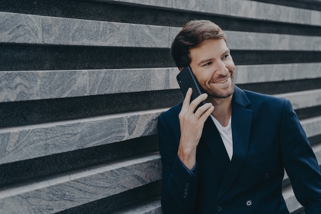 Aantrekkelijke jonge man kantoormedewerker in stijlvolle blazer die buiten op mobiele telefoon spreekt