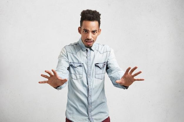 Aantrekkelijke jonge man maakt bang gebaar met handpalmen, verdedigt zichzelf