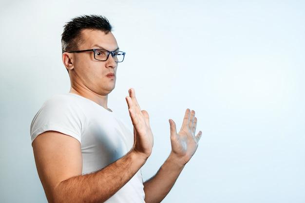 Aantrekkelijke jonge man maakt bang gebaar met palmen, verdedigt zich tegen iemand, vraagt om het onmiddellijk te stoppen.