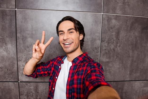 Aantrekkelijke jonge man maakt selfie foto en twee vingers tonen