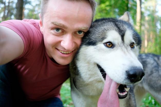 Aantrekkelijke jonge man maakt selfie met zijn hond malamute op een wandeling in het bos