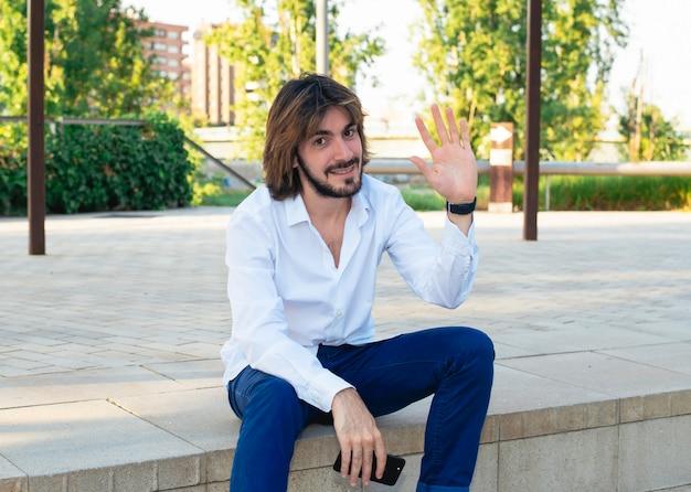 Aantrekkelijke jonge man met baard, met wit shirt heeft een smartphone in zijn hand en is in het park, glimlacht en golven