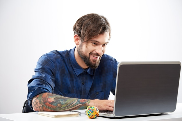 Aantrekkelijke jonge man met blauw shirt zitten met laptop en werken, freelance concept, portret.