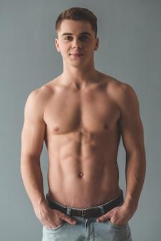 Aantrekkelijke jonge man met blote torso kijkt naar de camera.