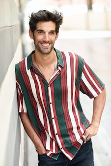 Aantrekkelijke jonge man met donker haar en modern kapsel dragen casual kleding buitenshuis