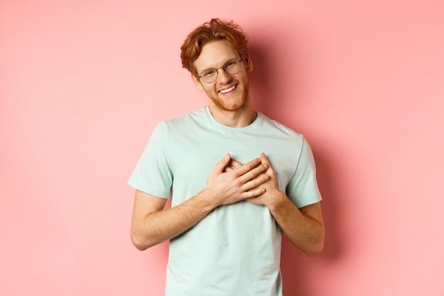 Aantrekkelijke jonge man met gemberhaar, hand in hand op het hart en dankbaar glimlachen, dank zeggen, dankbaarheid uitdrukken, over roze achtergrond staan.