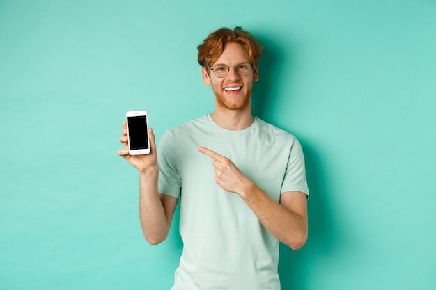 Aantrekkelijke jonge man met rode baard en haar wijzende vinger op het lege smartphonescherm, met online promotie of app, glimlachend in de camera, turkooizen achtergrond.