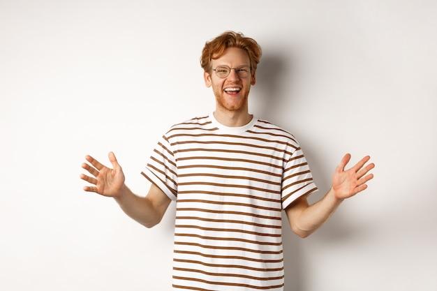 Aantrekkelijke jonge man met rood haar en een bril met grote omvang, lengte van het grote object, glimlachend tevreden, staande op een witte achtergrond.