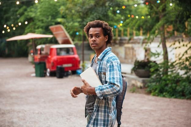 Aantrekkelijke jonge man met rugzak en boeken wandelen in het park