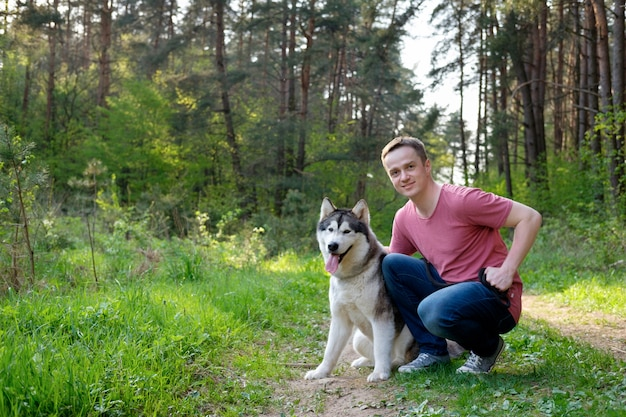 Aantrekkelijke jonge man met zijn hond malamute op een wandeling in het bos
