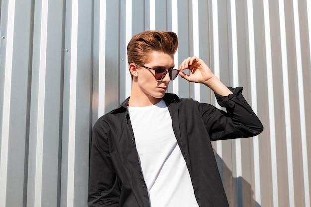 Aantrekkelijke jonge man model in een modieus zwart shirt in een t-shirt rechtzetten stijlvolle zonnebril. europese hipster kerel poseren in de buurt van een zilveren metalen muur in een stad op een zonnige dag. moderne stijl