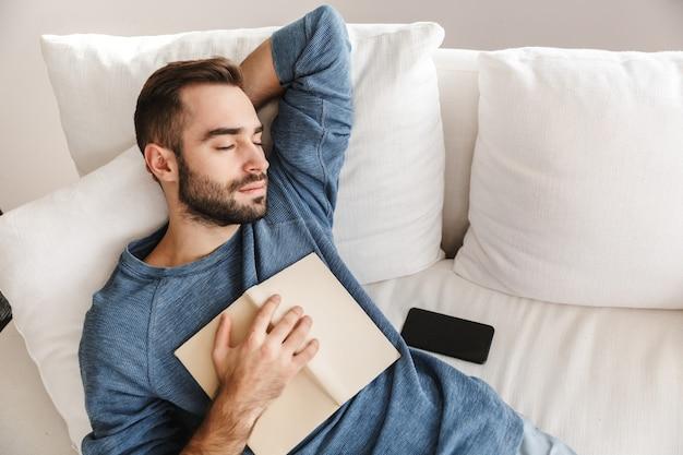 Aantrekkelijke jonge man ontspannen op een bank thuis, slapen