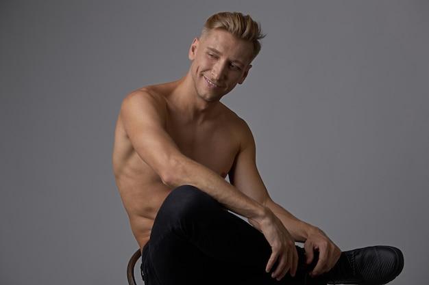 Aantrekkelijke jonge man poseren met naakte torso zittend op een stoel