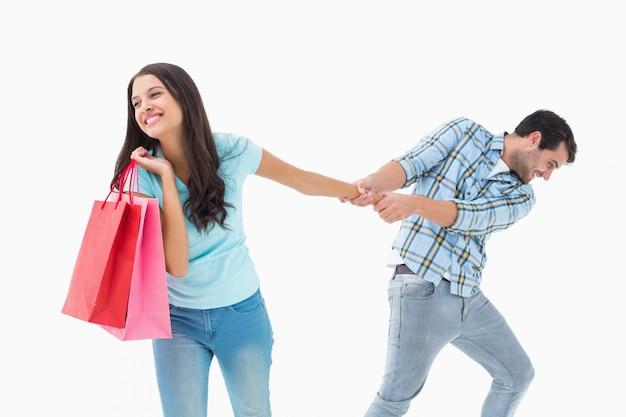 Aantrekkelijke jonge man trekt zijn shopaholic vriendin