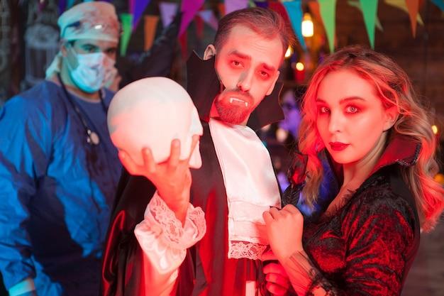 Aantrekkelijke jonge man verkleed als dracula met zijn mooie meisje voor halloween-feest. sexy vrouw verkleed als een heks voor halloween.