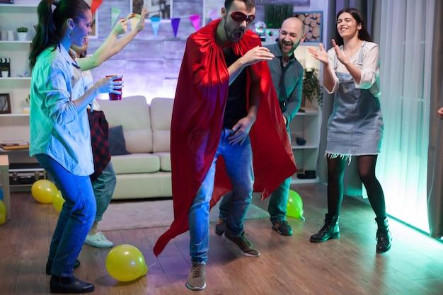 Aantrekkelijke jonge man verkleed als een superheld op een feestje met zijn vrienden.