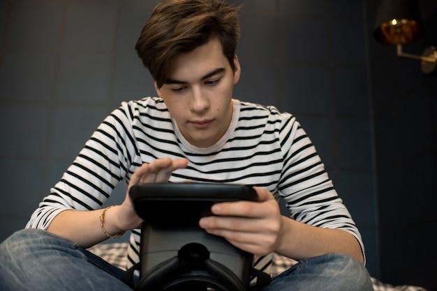 Aantrekkelijke jonge man zitten en houden van vr-bril