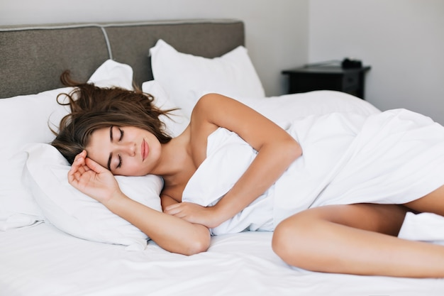 Aantrekkelijke jonge meisjesslaap op wit bed in modern appartement in de ochtend.