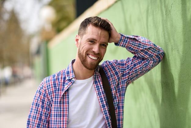 Aantrekkelijke jonge mens die in openlucht lacht. levensstijl concept.