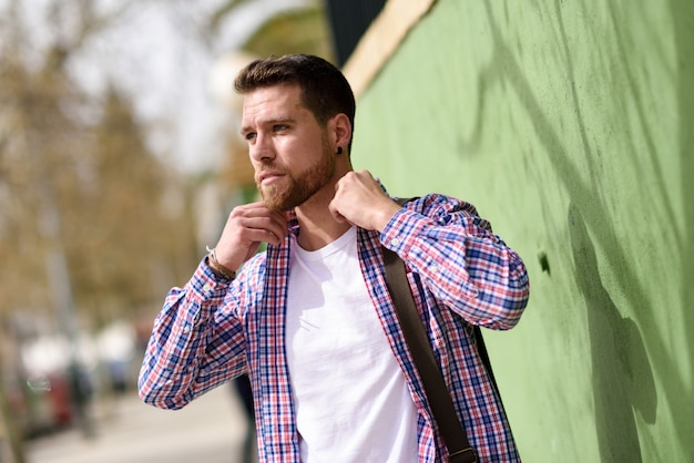 Aantrekkelijke jonge mens die zich op stedelijke achtergrond bevindt. levensstijl concept.