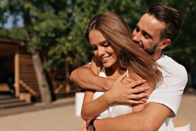 Aantrekkelijke jonge mensen knuffelen en kussen in zonlicht op het strand