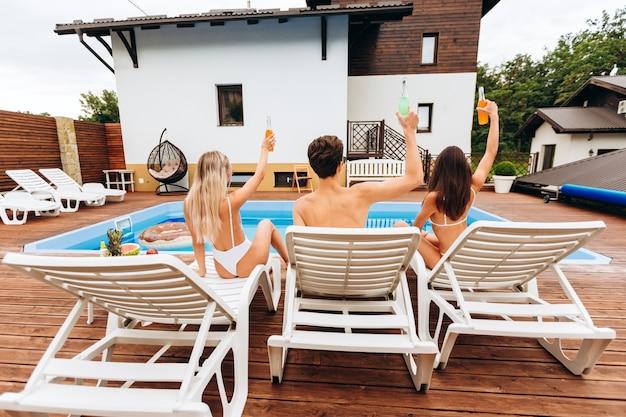 Aantrekkelijke jonge mensen vermaken zich bij het zwembad in een landelijk complex.