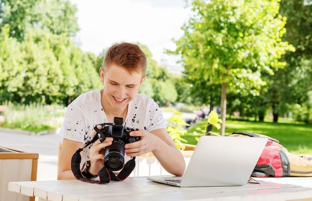 Aantrekkelijke jonge mensenstudent die laptop buiten met behulp van