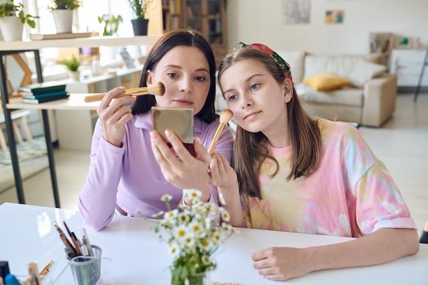 Aantrekkelijke jonge moeder en haar dochter die aan tafel zitten en één spiegel gebruiken tijdens het aanbrengen van rouge op gezicht met make-upborstel