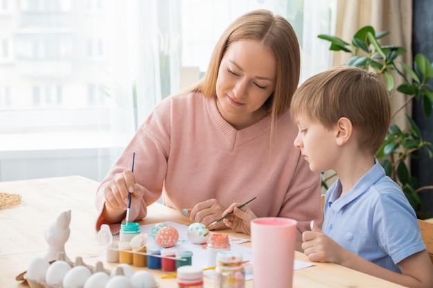 Aantrekkelijke jonge moeder en zoon schilderen eieren met felle kleuren tijdens de voorbereiding op pasen
