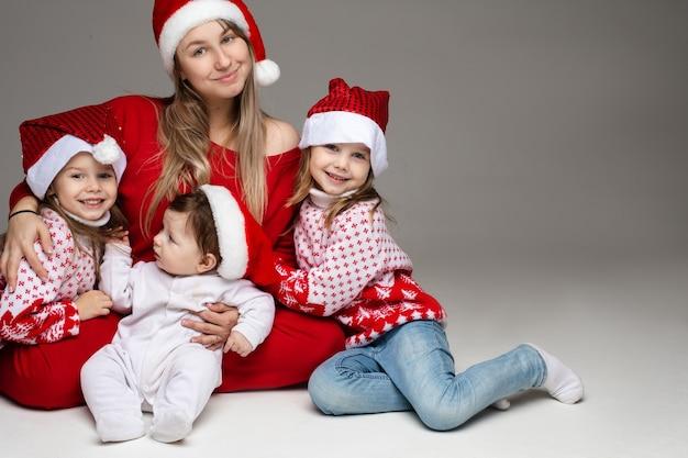 Aantrekkelijke jonge moeder in het rood omhelst haar twee dochters en zoontje in santa hoeden.