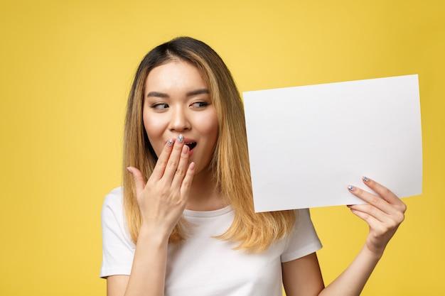 Aantrekkelijke jonge mooie aziatische studentenvrouw die leeg witboek houdt.