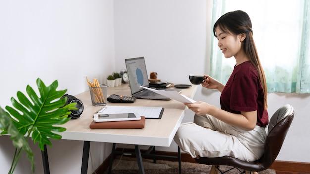 Aantrekkelijke jonge mooie aziatische vrouwenondernemer of freelancer die thuis met laptop bedrijfsrapporten en online mededelingen aan woonkamerbank werken, die op afstand toegangsconcept werken.