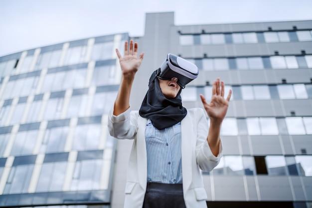 Aantrekkelijke jonge moslimonderneemster met sjaal op hoofd die vr-bril gebruikt voor virtuele presentatie. duizendjarige generatie.