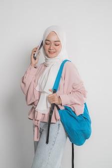 Aantrekkelijke jonge moslimstudent die mobiele telefoon met behulp van over wit geïsoleerde achtergrond