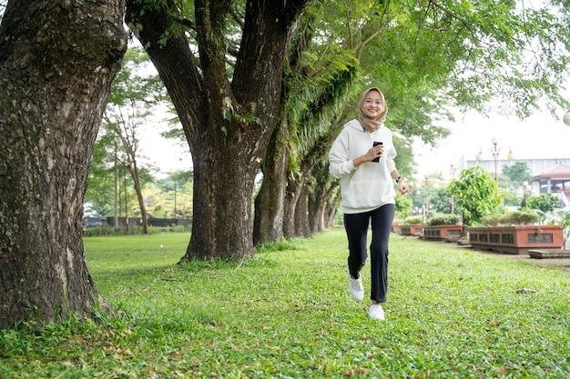 Aantrekkelijke jonge moslimvrouw die buiten loopt. lachende gelukkige aziatische sport meisje joggen