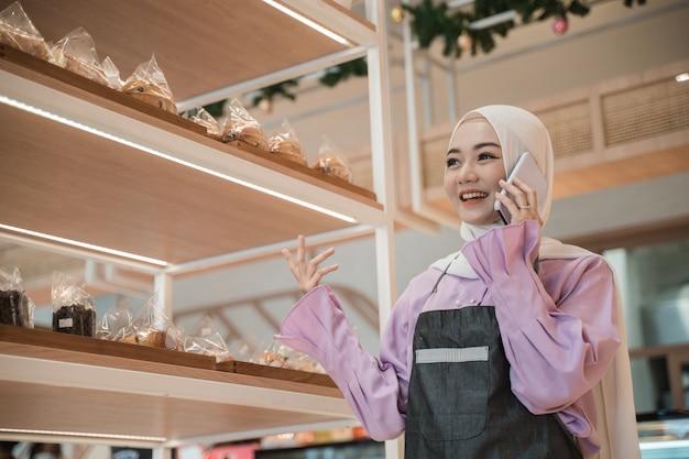 Aantrekkelijke jonge moslimvrouw die een telefoongesprek neemt terwijl in haar winkel. drukke zakenmedewerker