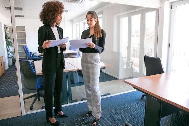 Aantrekkelijke jonge ondernemers die documentatie in handen bespreken. twee vrij zelfverzekerde vrouwelijke collega's houden papieren en staan in kantoorruimte. teamwork, bedrijfs- en managementconcept