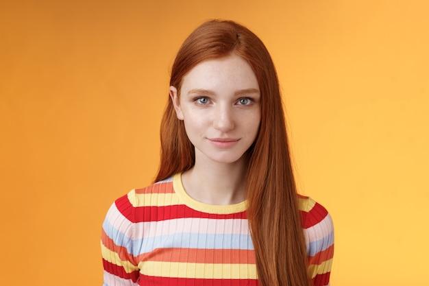 Aantrekkelijke jonge oprechte roodharige meisje schoon pure perfecte huidskleur glimlachen bescheiden blik camera vriendelijk opgetogen staan ontspannen wachten staren dom teder, poseren oranje achtergrond. kopieer ruimte