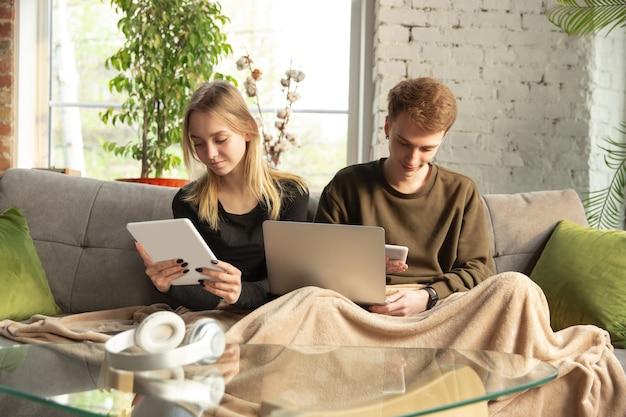 Aantrekkelijke jonge paar apparaten samen gebruiken, tablet, laptop, smartphone, communicatie, gadgets concept. technologieën die mensen verbinden in zelfisolatie. levensstijl thuis.