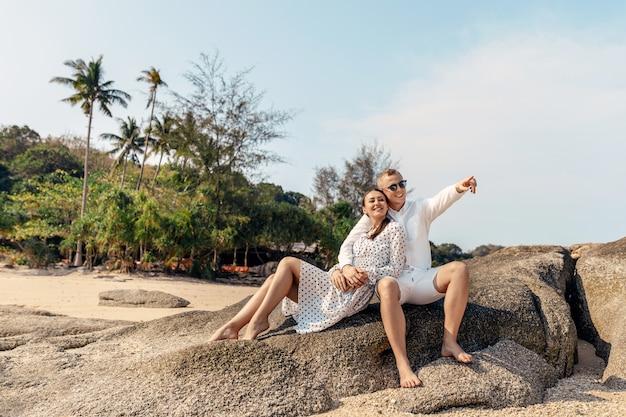 Aantrekkelijke jonge paar zittend op de rotsen op het strand