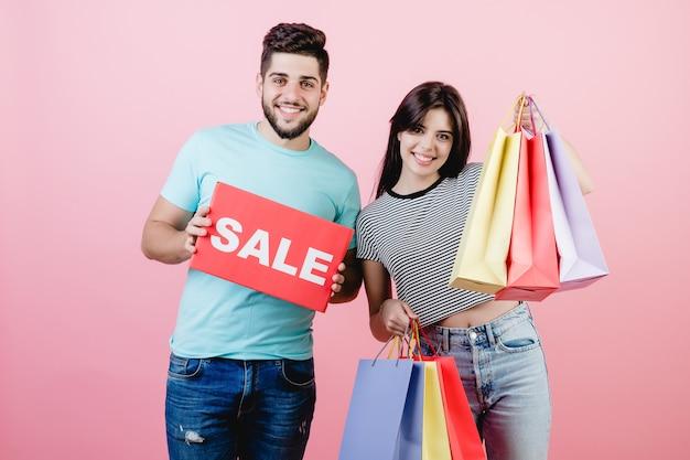 Aantrekkelijke jonge paarman en vrouw met verkoopteken en kleurrijke het winkelen zakken