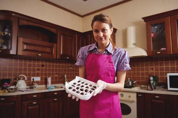 Aantrekkelijke jonge roodharige banketbakker draagt een roze schort, staande in het midden van haar huiskeuken met een doos met handgemaakte chocoladetruffels