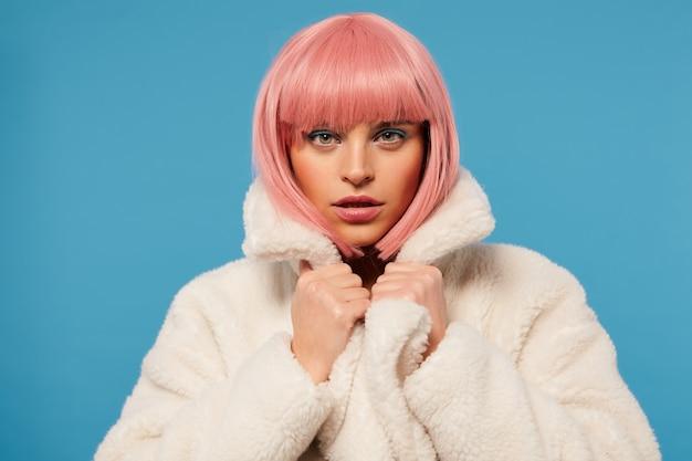 Aantrekkelijke jonge roze haired vrouw met bob kapsel, gekleed in gekleurde make-up, hand op de kraag van haar witte jas en op zoek