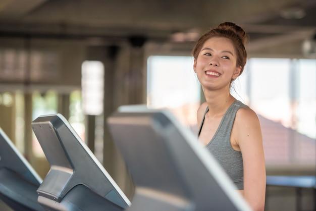 Aantrekkelijke jonge sportenvrouw die op tredmolen in gymnastiek, gezondheidszorgconcept lopen.