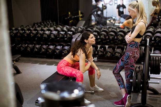 Aantrekkelijke jonge sportieve gerichte fitness womanl die bicepsenoefeningen doet