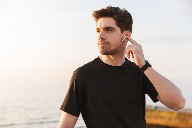 Aantrekkelijke jonge sportman in zwart overhemd in oortelefoons