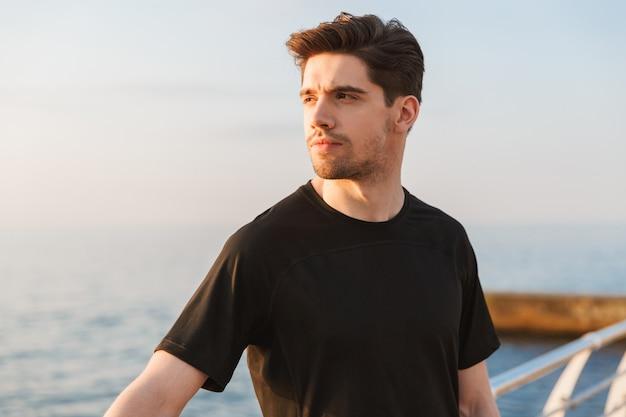 Aantrekkelijke jonge sportman in zwarte t-shirt in oortelefoons