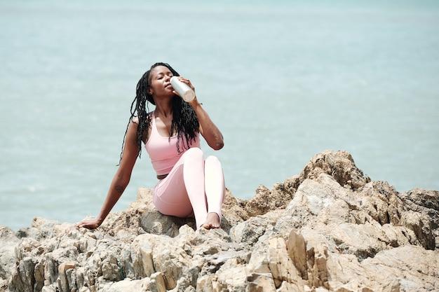 Aantrekkelijke jonge sportvrouw die op rotsen zit en zoet water drinkt na het sporten op het strand