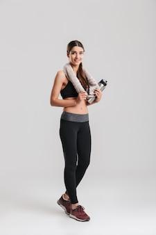 Aantrekkelijke jonge sportvrouw die van gemiddelde lengte trainingspak met handdoek draagt en fles met nog water kijkt, dat over grijze muur wordt geïsoleerd